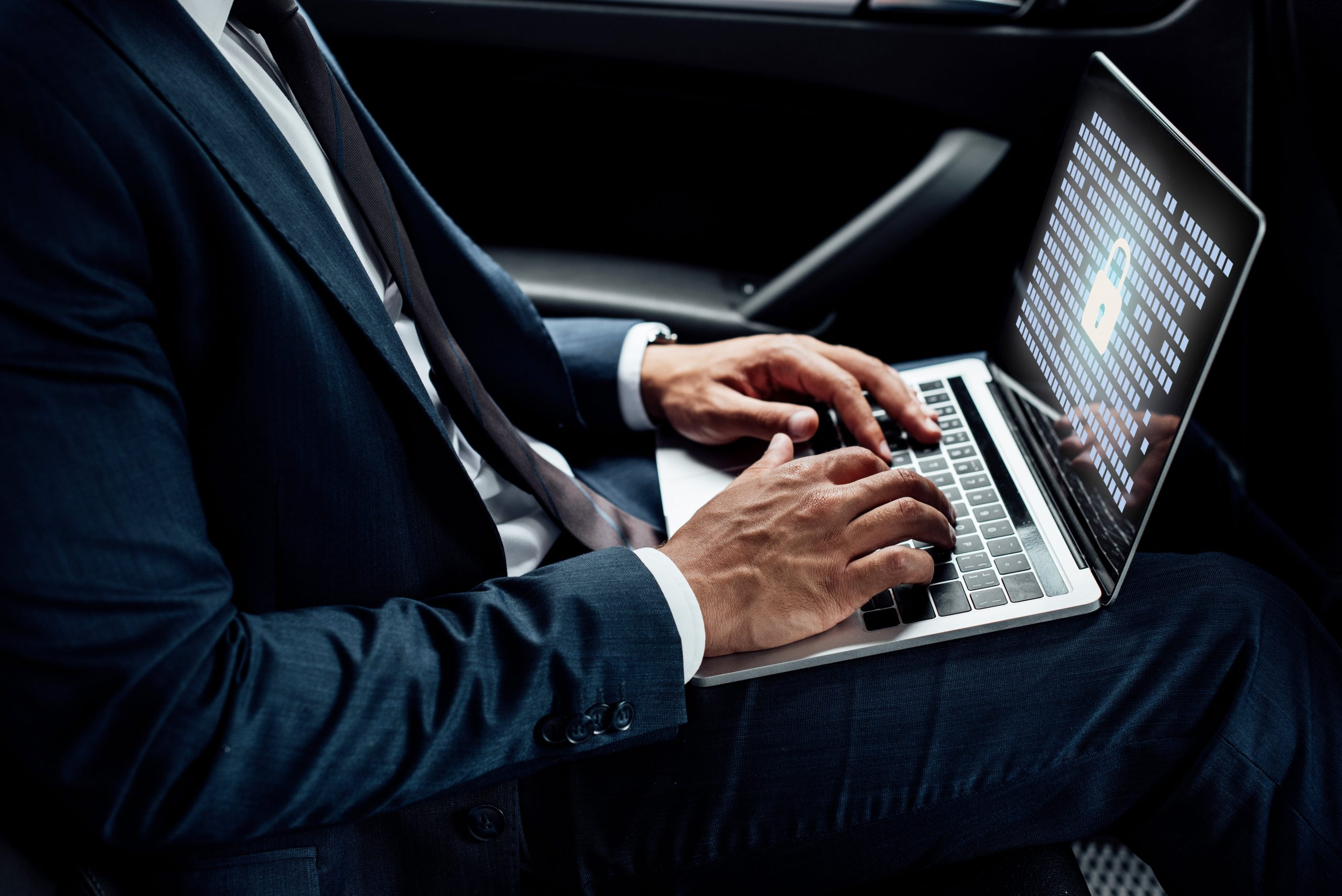 Man working on Laptop computer driving to New York